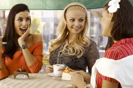 Tres amigas charlando en el caf� al aire libre junto a la mesa. photo