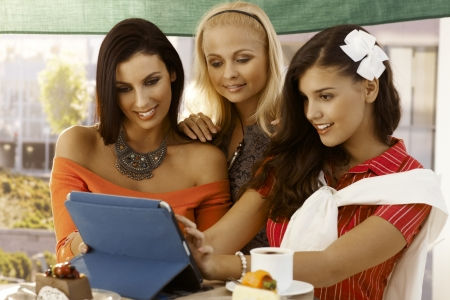 Young women using tablet computer outdoors, smiling happy. photo