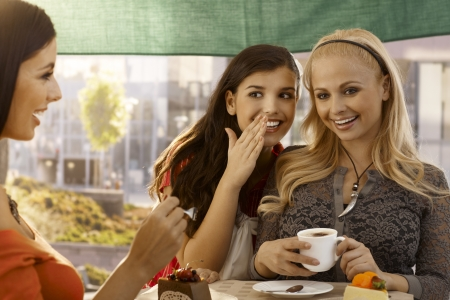 Happy female friends chatting, whispering at cafe, having cake and coffee outdoors. photo