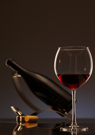 winetasting: Elegant photo of a glass of red wine with bottle in background. Stock Photo