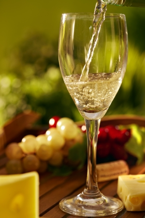 Outdoor still life photo of a glass of white wine and cheese on a wooden tray, photo