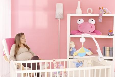 vivero: Madre embarazada sentada en un sillón en la habitación de color rosa bebé, pensando.