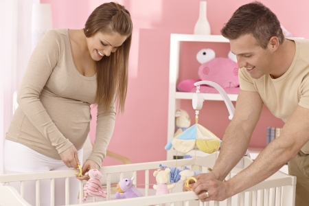 Pregnant mother and husband preparing baby's cot, smiling. photo