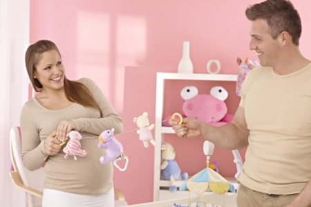Young couple preparing baby's room, having fun. photo