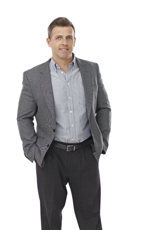 Businessman standing with hands in pockets, smiling. photo