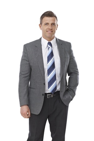 Portrait of elegant businessman standing with hands in pockets over white background. photo