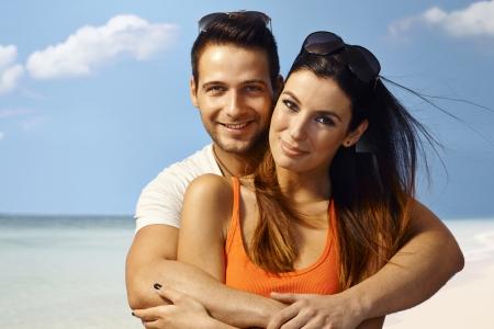 cuddling: Happy loving couple enjoying summer holiday on the beach, smiling happy, looking at camera.
