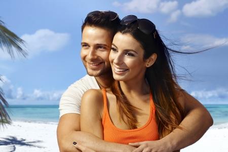 Young couple hugging on the beach, having fun, enjoying summer holiday, looking away.