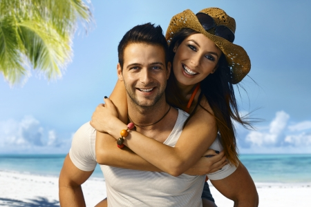 Attractive young loving couple enjoying summer holiday on the beach piggyback, photo