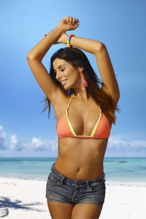 Sexy young woman enjoying summer holiday and sun on the beach eyes closed in bikini. photo