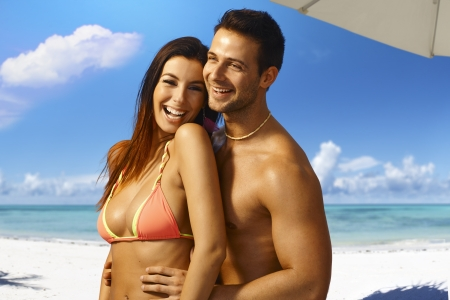 bikini couple: Happy young loving couple on summer holiday, embracing and smiling on the beach.