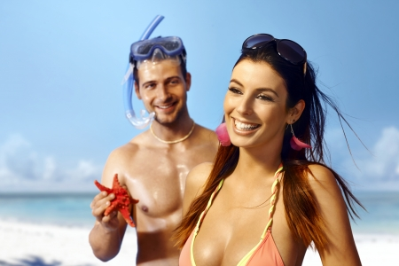 starfish beach: Beautiful young woman smiling happy on the beach, boyfriend holding sea star in hand. Stock Photo