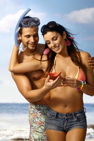 Loving couple hugging on beach, holding sea star. Man in snorkel.