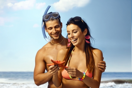 Happy loving couple on beach holding sea star, smiling. Man scuba-diving.