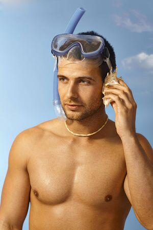 murmur: Closeup portrait of handsome scuba diver listening to murmur of sea in seashell.