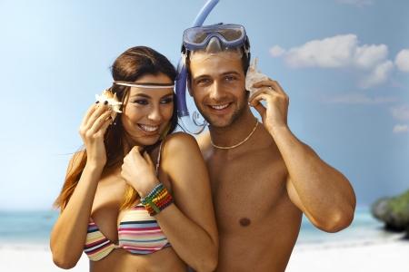 murmur: Happy loving couple hugging on the beach, listening to murmur of sea in seashell, smiling.