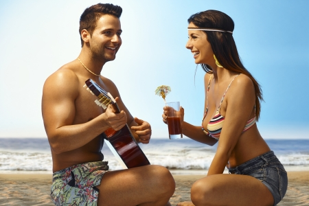 Young couple on the beach. Man playing guitar, woman drinking cocktail, enjoying time together. photo
