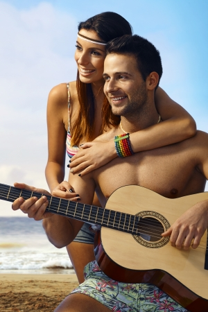 black man white woman: Happy romantic couple enjoying time together on the beach at summertime, man holding guitar.