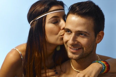 Happy young loving couple outdoors at summertime, woman kissing man on the face. Stock Photo
