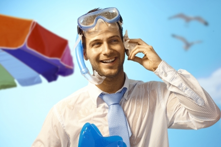 murmur: Happy young businessman on summer holiday listening to murmur of sea in seashell. Stock Photo