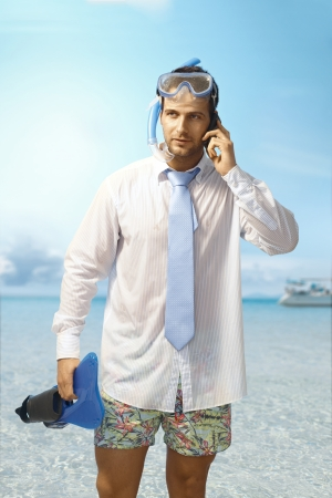 Young businessman on the beach having phone call, wearing shirt and tie and scuba diving equipments.