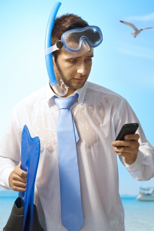mobilephone: Workaholic young businessman using mobilephone on summer holiday. Stock Photo