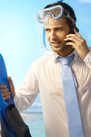 Workaholic young businessman on mobilephone on summer holiday, wearing shirt and tie and scuba diving equipments. photo