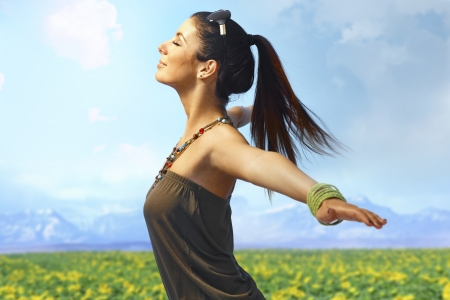 outspreading: Attractive young woman enjoying summer sun and wind on the meadow. Side view, pretending to fly.