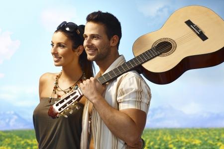 black man white woman: Romantic loving couple walking on the meadow, man holding guitar, smiling happy. Stock Photo