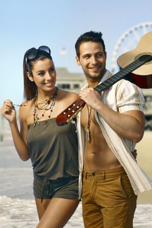 Happy loving couple embracing, walking on the beach, smiling happy, man holding guitar. photo
