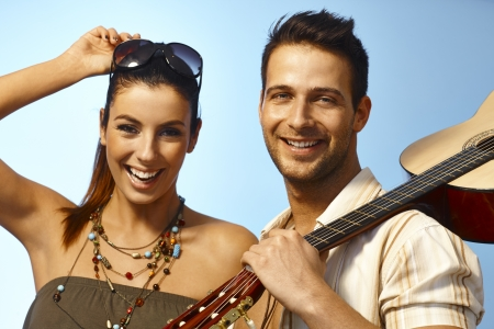 Closeup summer portrait of happy loving couple looking at camera, man holding guitar. photo