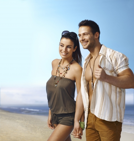 seasonal clothes: Romantic young couple walking on the beach hand in hand, smiling happy.