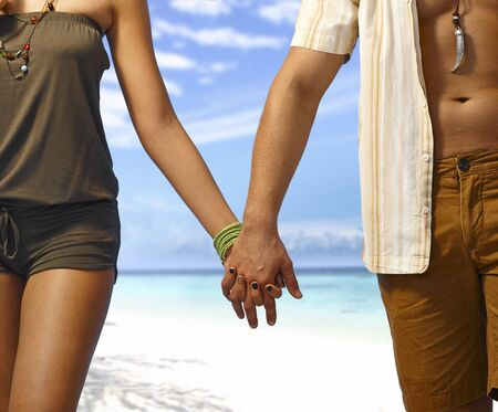 boy body: Closeup hand in hand, young couple walking on the beach at summertime. Only body part.