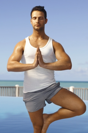 Athletic young man practicing yoga on the coast, meditating eyes closed in tree pose. photo
