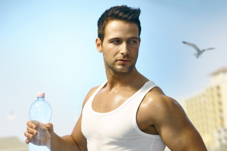 Young athletic man jogging outdoors, holding water bottle. Stock Photo - 19365652