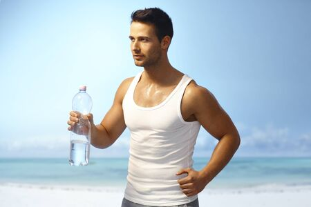 Handsome young man jogging on the coast, holding water bottle. photo