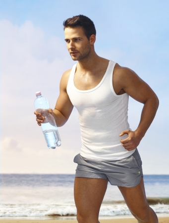 Athletic young man in shorts jogging on the beach, holding water bottle. photo