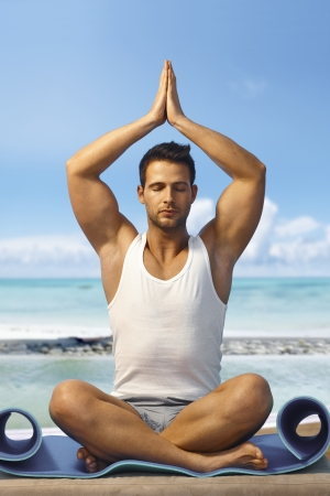 Athletic young man practicing yoga on the beach, meditating in prayer position eyes closed. photo