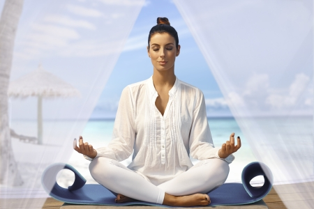 Beautiful young woman meditating on the beach eyes closed. Stock Photo - 19365625