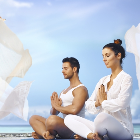 meditating: Young couple meditating outdoors, sitting eyes closed in prayer position. Stock Photo