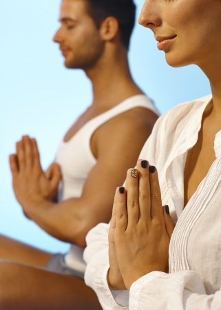holistic view: Closeup photo of meditating people, woman with extravagant nail polish.