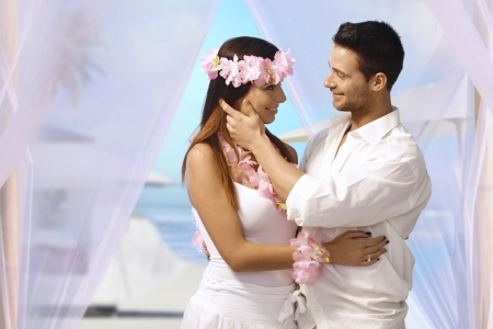 Happy couple having dream wedding on tropical island, embracing, caressing each other.