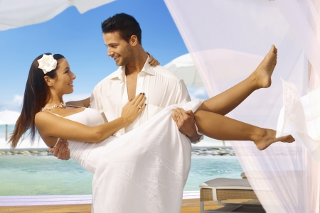 Young man holding beautiful bride in arms after dream wedding on tropical island, both smiling happy.