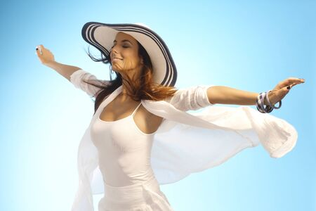 outspreading: Attractive young woman pretending to fly, enjoying sun and wind eyes closed.