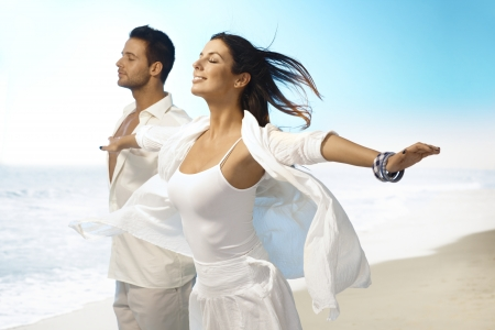 outspreading: Young couple enjoying summer sun and wind on the beach. Pretending to fly eyes closed, arms wide open, smiling. Stock Photo