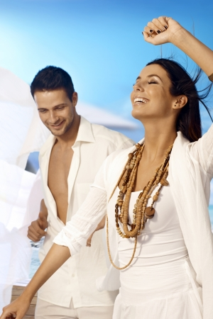 pareja bailando: Baile de la mujer hermosa con los ojos cerrados en la playa, el hombre mirando.
