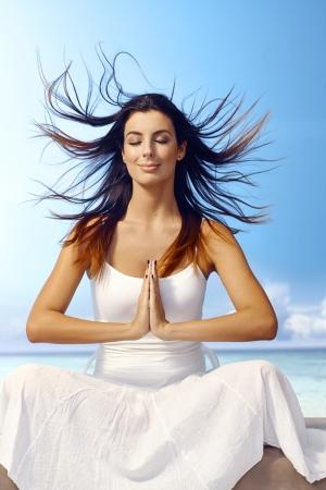 mujer meditando: Atractiva joven meditando en la playa cerró los ojos, el pelo que sopla el viento, sonriente, sentado en posición de oración.