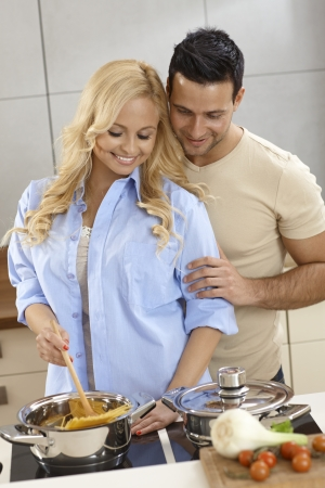loving couple: Happy loving couple cooking spaghetti in kitchen, hugging.