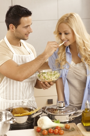 Attractive young couple cooking together in kitchen, woman tasting salad. Stock Photo