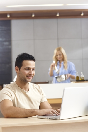 Young man sitting at table, using laptop computer at home, female cooking at background. photo